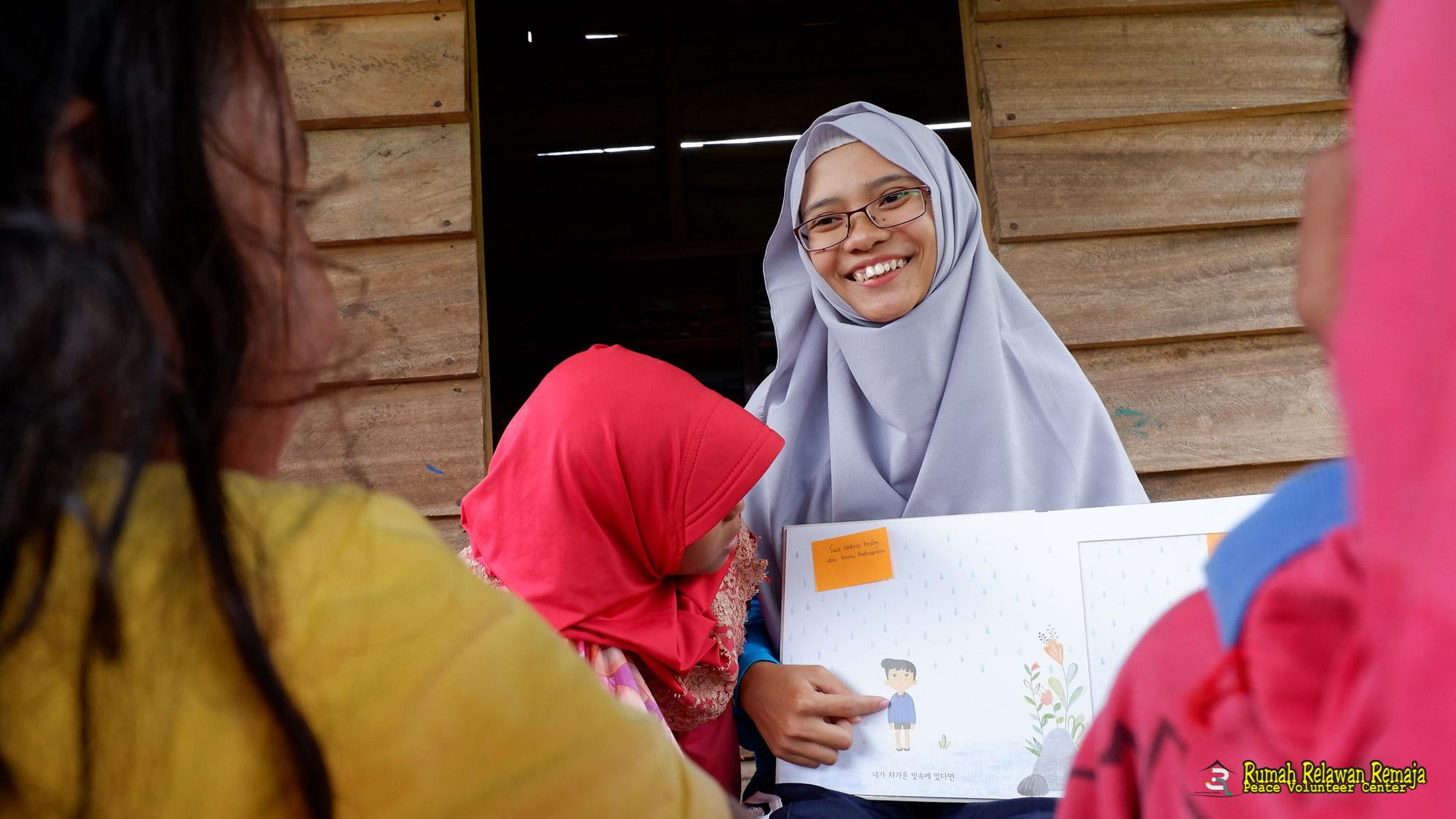 Dinda Triani, sedang membacakan buku dongeng bersama anak-anak desa Lapeng, Pulo Aceh